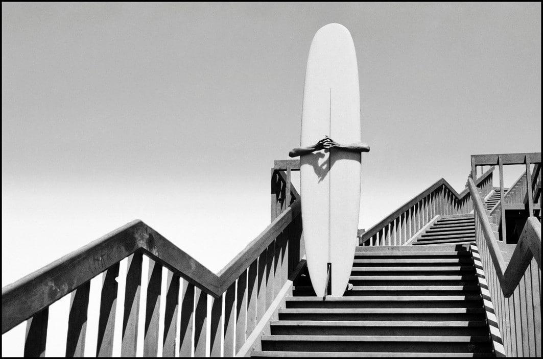 USA. California. 1968. Man holding a surfboard on beach steps in Corona Del Mar.