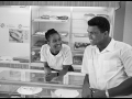 USA. Chicago, Illinois. 1966. Muhammad Ali (then Cassius Clay), boxing world heavy weight champion. Ali flirts with Belinda in a bakery shop. Belinda later became Ali's second wife.